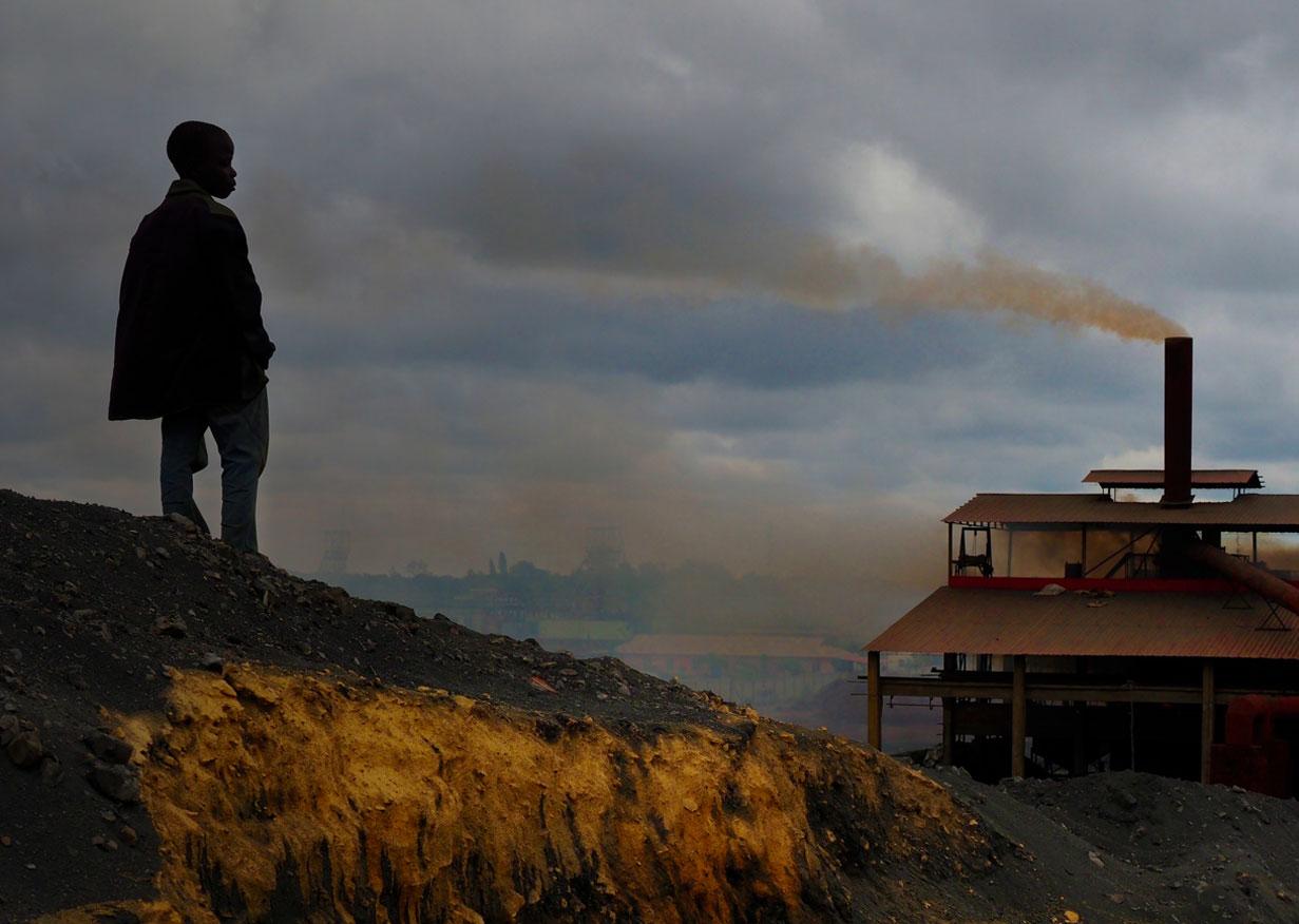 Kabwe, Zambia. Black Mountain: Boy on slag heap overlooking smelter